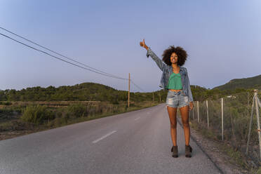 Young woman standing on street and hitchhiking in the evening, Ibiza - AFVF04396