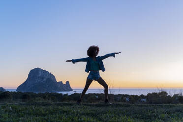 Young woman standing on a meadow doing yoga at sunset, Ibiza - AFVF04402
