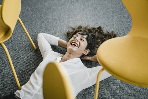 Laughing businesswoman laying in an office on the floor between chairs - KNSF06867