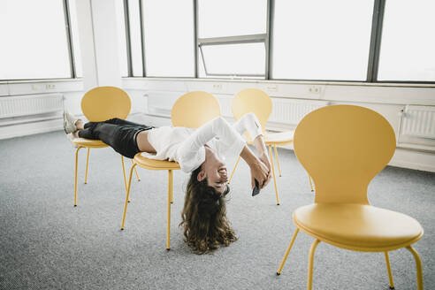 Smiling businesswoman lying across chairs in an empty office using smartphone - KNSF06873