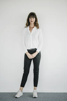 Smiling businesswoman standing in front of a white wall - KNSF06876