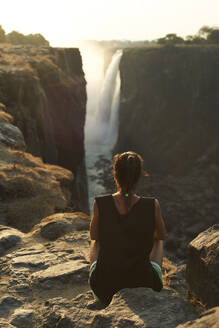 Woman sitting on the top of a rock enjoying the Victoria Falls at sunset, Zimbabwe - VEGF01056