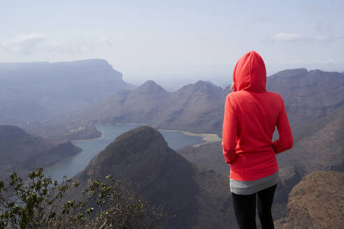 Woman standing on top of a hill enjoying the beautiful landscape below her, Blyde River Canyon, South Africa. - VEGF01062