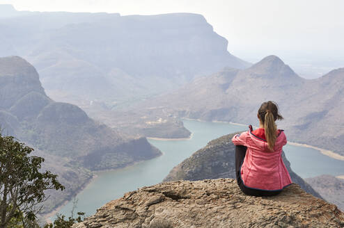 Woman sitting on a rock enjoying the beautiful landscape below her, Blyde River Canyon, South Africa. - VEGF01065