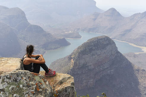 Woman sitting on a rock with beautiful landscape as background, Blyde River Canyon, South Africa - VEGF01068