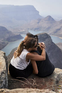 Two women hugging on a rock with beautiful landscape as background, Blyde River Canyon, South Africa - VEGF01071