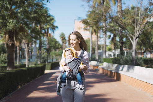 Mother walking with baby boy in sling outdoors - ERRF02234
