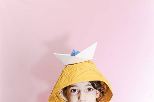 Little girl wearing an oilskin and carrying a paper boat on her head - ERRF02288