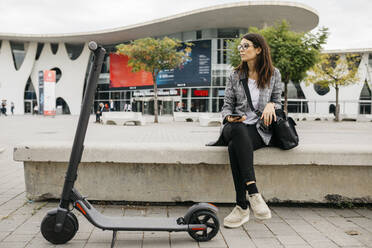 Young businesswoman holding smartphone next to an e-scooter in the city - JRFF03906