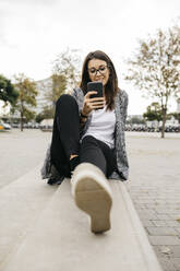 Young businesswoman using smartphone, sitting on bench in the city - JRFF03909