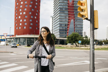 Young businesswoman with e-scooter in the city - JRFF03912