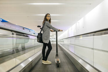 Businesswoman with her electric scooter on moving walkway - JRFF03915