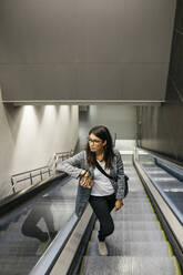 Businesswoman standing on escalator of a subway station - JRFF03924