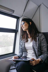 Brunette woman while traveling by train to work, with a tablet in her hands - JRFF03930
