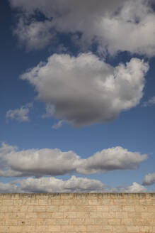 Spain, Mallorca, Low angle view of clouds floating over brick wall - JMF00477