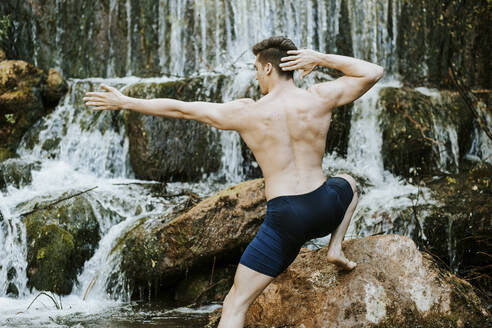 Rear view of young man practicing yoga on a waterfall - MIMFF00008