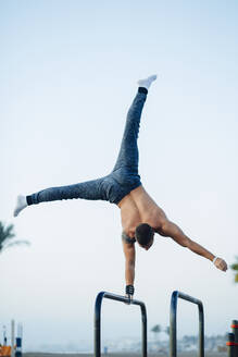 Young man practicing calisthenics at an outdoor gym - MIMFF00017