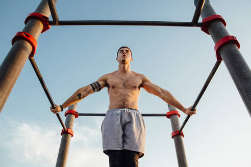 Young man practicing calisthenics at an outdoor gym - MIMFF00020