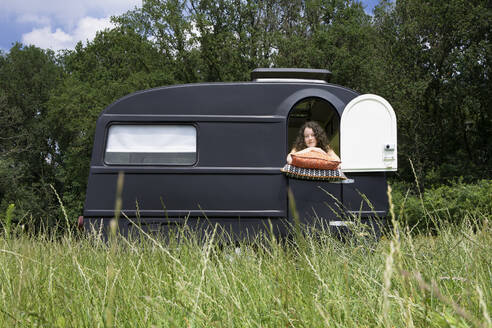 Young woman looking out of caravan standing on a meadiow - PSTF00485