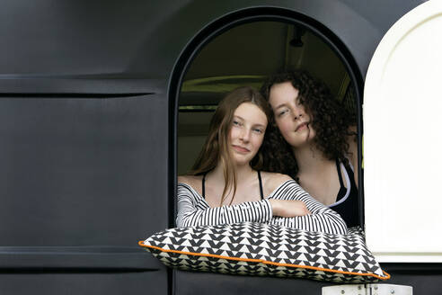 Portrait of two best friends looking out of caravan - PSTF00488