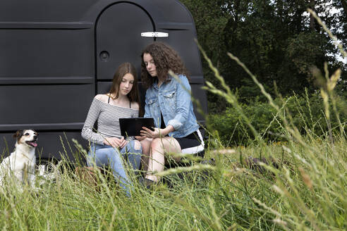 Two friends sitting on a meadow in front of black caravan looking at digital tablet - PSTF00491