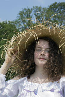 Portrait of young woman wearing frayed straw hat in nature - PSTF00497