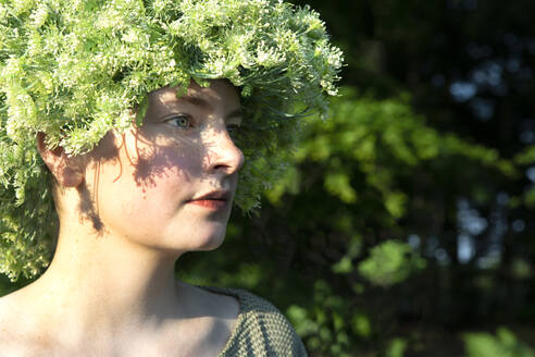 Portrait of young woman wearing headpiece of flowers - PSTF00572
