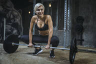 Blond sportswoman with barbell in gym - MADF01441