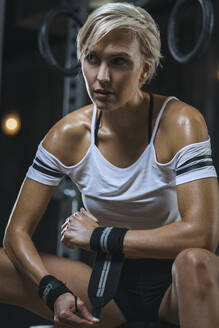 Portrait of blond sportswoman wearing white t-shirt and sweatband in gym - MADF01447