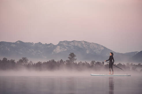 Woman stand up paddling on lake Kirchsee at morning mist, Bad Toelz, Bavaria, Germany - WFF00196