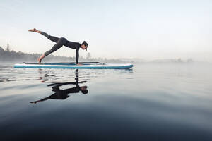 Woman practicing paddle board yoga on lake Kirchsee in the morning, Bad Toelz, Bavaria, Germany - WFF00199