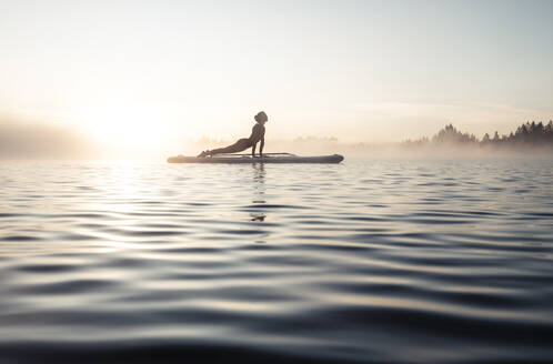 Woman practicing paddle board yoga on lake Kirchsee in the morning, Bad Toelz, Bavaria, Germany - WFF00202