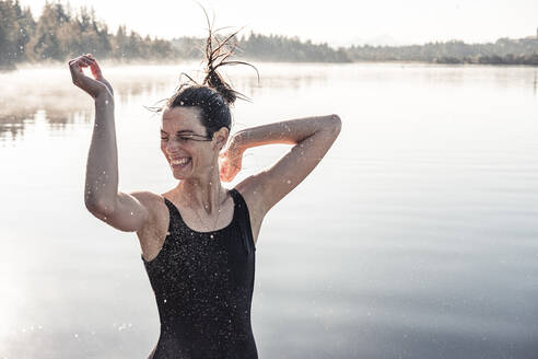 Cheerful woman wearing black swimsuit at a lake at morning mist - WFF00217