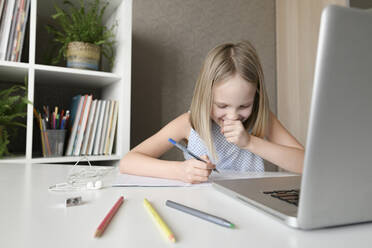 Laughing girl sitting at table at home doing homework and using laptop - EYAF00748