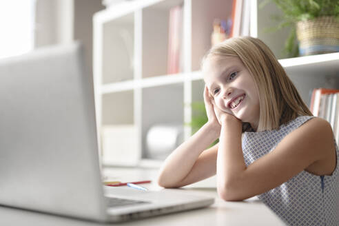 Happy girl sitting at table at home using laptop - EYAF00754