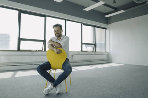 Portrait of confident mature businessman sitting on yellow chair in empty office - KNSF06883