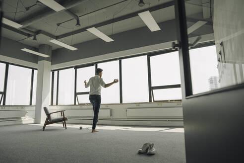 Mature businessman practicing yoga in empty office - KNSF06907