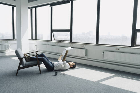 Mature businessman lying on the floor in empty office using laptop - KNSF06928