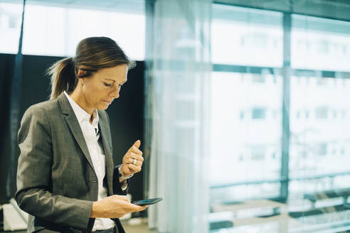 Serious businesswoman text messaging on smart phone at workplace - MASF15057