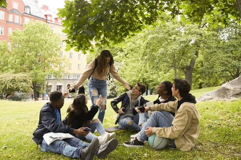 Happy teenage girl gesturing while standing by friends sitting on land at park - MASF15138