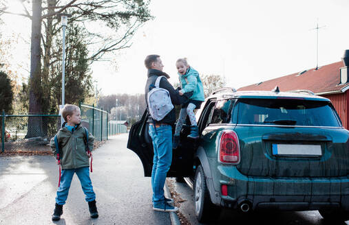 Father dropping his kids off at school in the morning - CAVF69969