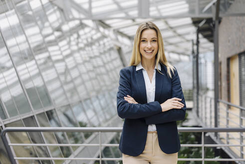 Portrait of a smiling young businesswoman in a modern office building - JOSF03823