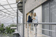 Two young businesswomen sharing tablet in modern office building - JOSF03829