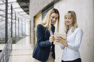 Two happy young businesswomen with tablet in modern office building - JOSF03832