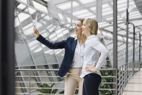 Two happy young businesswomen using a tablet in office - JOSF03838