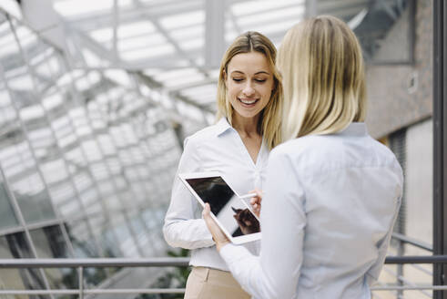 Two young businesswomen with tablet talking in modern office building - JOSF03850