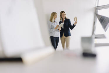 Two young businesswomen with tablet and house model talking in office - JOSF03859