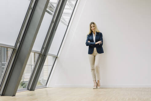 Portrait of a smiling young businesswoman leaning against a wall in a modern office building - JOSF03865