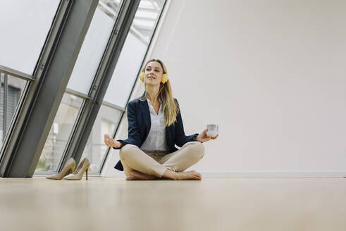 Young businesswoman practicing yoga in office - JOSF03868