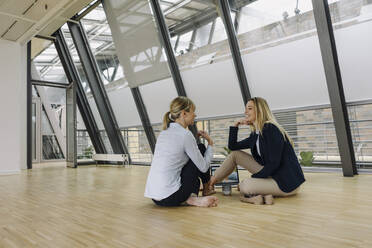 Two smiling young businesswomen sitting on the floor and talking in office - JOSF03871